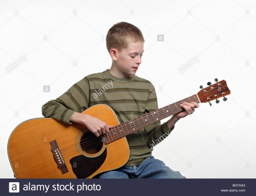 elementary-age-child-sitting-and-playing-a-large-acoustic-guitar-BH7XA3